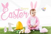 Fotografie cute baby in bunny costume sitting near colorful chicken eggs, tulips and yellow ostrich egg with happy Easter lettering and rabbits illustration