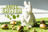 decorative rabbit on green grass near golden chicken and quail eggs with happy Easter illustration