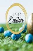 blue painted quail eggs on green grass near golden chicken egg and happy Easter lettering in circle