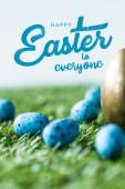 kék festett fürjtojással a zöld fű közelében arany csirke tojást és Boldog Húsvétot mindenkinek betűkkel