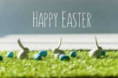 decorative bunnies on green grass near blue quail eggs with happy Easter lettering