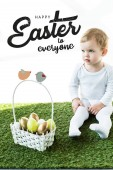 Fotografia child sitting on green grass near basket with Easter eggs and happy Easter to everyone lettering above