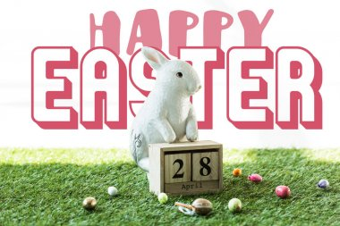 decorative rabbit, wooden calendar with 28 April date, and colorful Easter eggs on green grass with happy Easter lettering