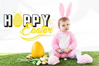 cute baby in bunny costume sitting near colorful chicken eggs, tulips and yellow ostrich egg with happy Easter lettering
