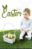 child sitting on green grass near basket with Easter eggs and happy Easter lettering above
