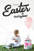 Fényképek aranyos baba ül a doboz közelében színes fürjtojással, játék nyúl és a levegő léggömb fehér háttér Boldog Húsvétot mindenkinek betűkkel