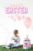 Fényképek aranyos baba ül a doboz közelében színes fürjtojással, játék nyúl és a levegő léggömb fehér háttérrel Boldog húsvéti betűkkel