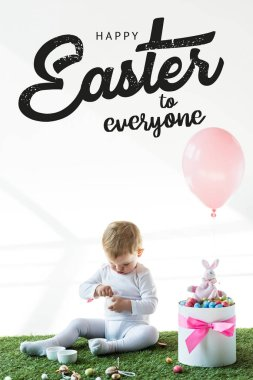 cute baby sitting near box with colorful quail eggs, toy rabbit and air balloon on white background with happy Easter to everyone lettering