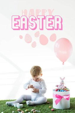 cute baby sitting near box with colorful quail eggs, toy rabbit and air balloon on white background with happy Easter lettering