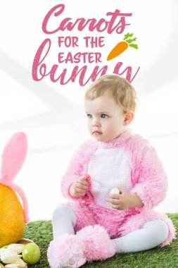 cute baby in bunny costume sitting on green grass with carrots for the Easter bunny lettering above