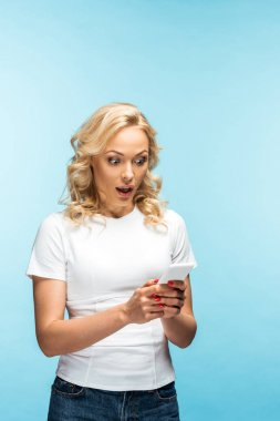Shocked blonde woman looking at smartphone and standing on blue stock vector