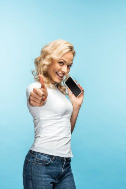 attractive blonde woman showing thumb up while holding smartphone with blank screen on blue