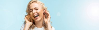 panoramic shot of cheerful woman with closed eyes listening music in earphones and singing on blue