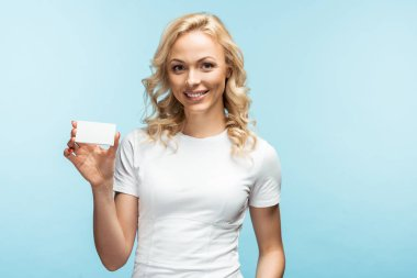 Cheerful blonde woman smiling while holding empty card on blue stock vector