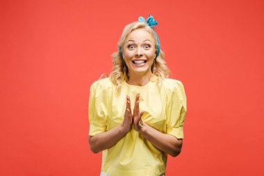 excited blonde woman in blue headband clapping hands on red