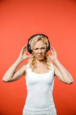 Displeased blonde woman listening music in headphones on red stock vector
