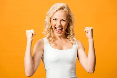 excited blonde woman looking at camera and celebrating triumph isolated on orange