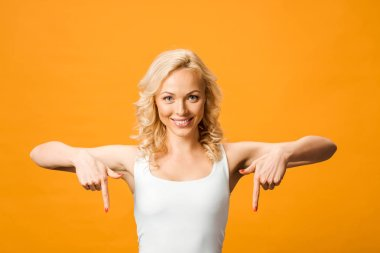 attractive woman looking at camera and pointing with fingers isolated on orange