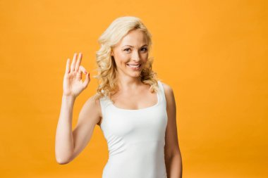 cheerful curly woman looking at camera and showing ok sign isolated on orange