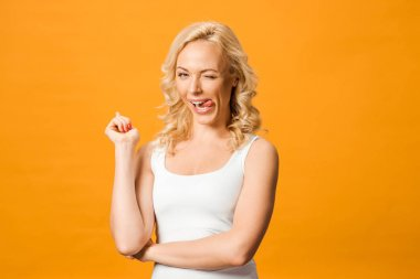 Happy blonde woman showing tongue while looking at camera isolated on orange stock vector