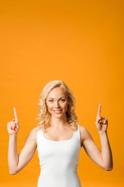 Smiling blonde woman pointing with fingers while looking at camera isolated on orange stock vector