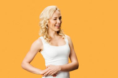 happy blonde woman smiling and standing isolated on orange
