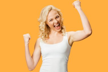 Happy blonde woman gesturing while celebrating triumph isolated on orange stock vector