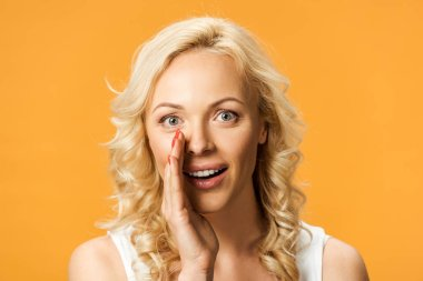 attractive blonde woman looking at camera and gossiping isolated on orange
