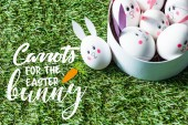 Fotografie chicken eggs with funny bunny faces and paper ears in bowl on green grass background with carrots for easter bunny lettering