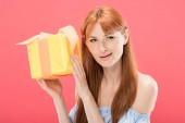 Kíváncsi vöröshajú születésnapi lány gazdaság sárga ajándékdoboz szalaggal izolált rózsaszín