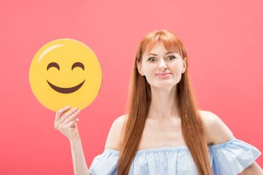 KYIV, UKRAINE - MAY 23, 2019: front view of cheerful redhead girl holding smiley isolated on pink stock vector