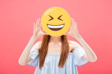 KYIV, UKRAINE - MAY 23, 2019: front view of redhead girl holding laughing smiley isolated on pink stock vector