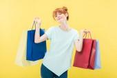 usmívající se zrzavá dívka držící nákupní tašky s očima izolovanými na žluté