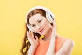 přitažlivá rudovlasá žena naslouchající hudbu ve sluchátkách a usmívající se izolovaná na žluté