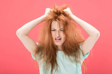 Angry redhead woman touching tangled hair and screaming isolated on pink stock vector