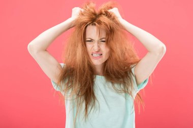 angry redhead woman with tangled hair waving hands isolated on pink