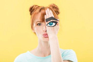 Front view of redhead girl holding paper eye and eyebrow and looking at camera isolated on yellow stock vector