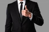 vista parziale delluomo daffari in abito nero mostrando il pollice in su isolato sul grigio