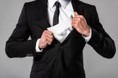 Fotografie Ausgeschnittene Ansicht des Geschäftsmannes im schwarzen Anzug mit weißer Maske isoliert auf grau