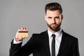 Selbstbewusster Geschäftsmann im schwarzen Anzug hält Kreditkarte isoliert auf grau