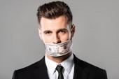 fekete öltönyt üzletember a forint bankjegyekkel a szürkére izolált szájjal