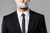 vista ritagliata di uomo daffari in abito nero con banconota dollaro sulla bocca isolata sul grigio