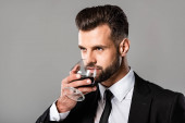 handsome businessman in black suit tasting whiskey isolated on grey