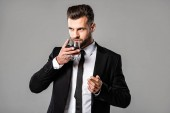 handsome businessman in black suit drinking whiskey isolated on grey