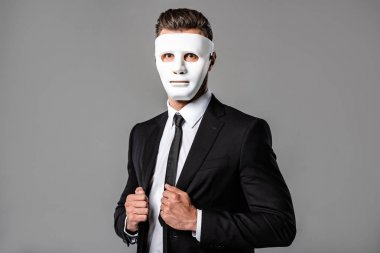 Businessman in black suit and white mask isolated on grey stock vector