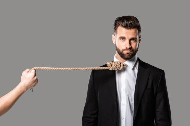 depressed businessman in black suit with noose on neck near murderer with rope isolated on grey