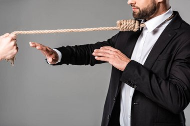 cropped view of businessman in black suit with noose on neck showing stop gesture to murderer with rope isolated on grey