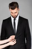 Dámský fixační knoflík na úspěšném podnikatele černý oblek izolovaný na šedé