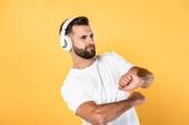 pohledný muž v bílém tričku naslouchající hudbě ve sluchátkách a tanci izolovaný na žlutém