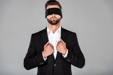 stylish handsome blindfolded businessman in black suit isolated on grey